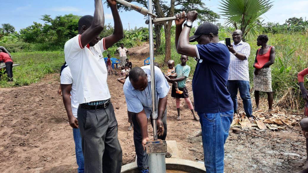 Three workers stand at the borehole and hold the stainless steel rod for the hand pump.
