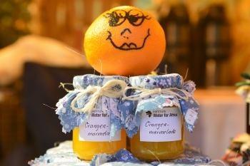 Zwei Gläser Orangenmarmelade mit Orange oben drauf
