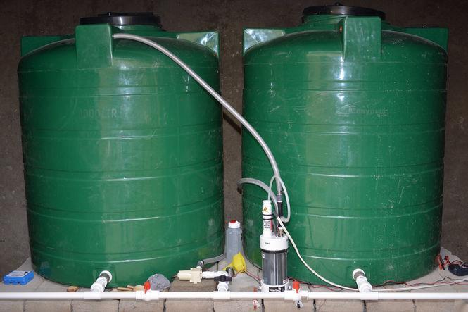 Zwei grüne Tonnen zur Wasseraufbereitung. Davor ein kleines Gerät für die Chlorung.