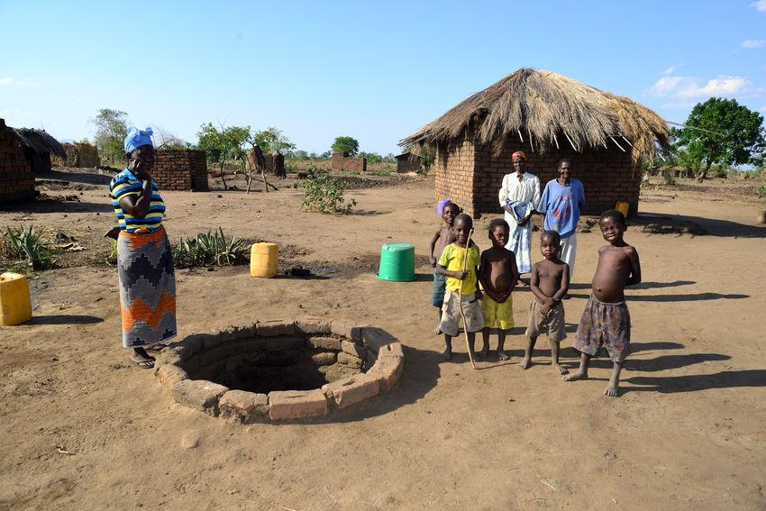 A woman with her children is standing at a well to get water