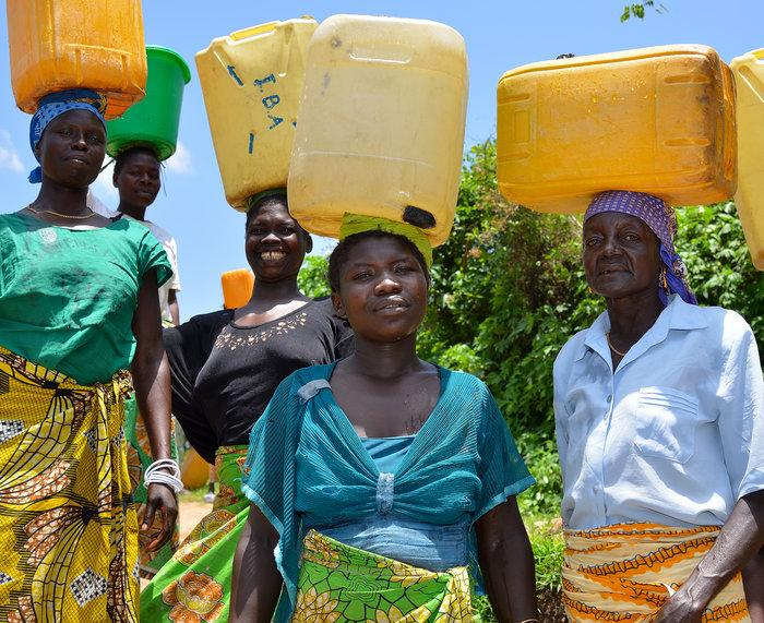 In Africa women have the task of fetching water. Here five women with water canisters on their heads.