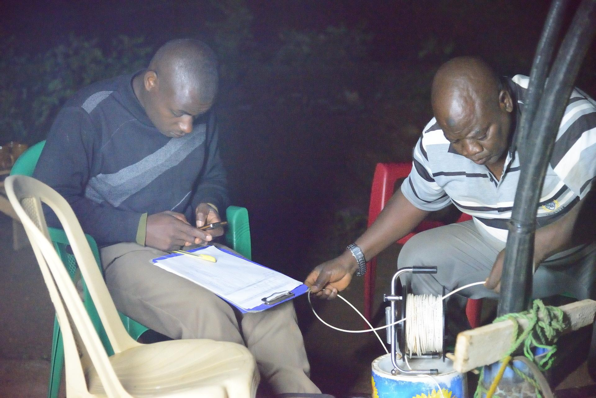 Two workers sit at night during the pumping test and note down the readings.