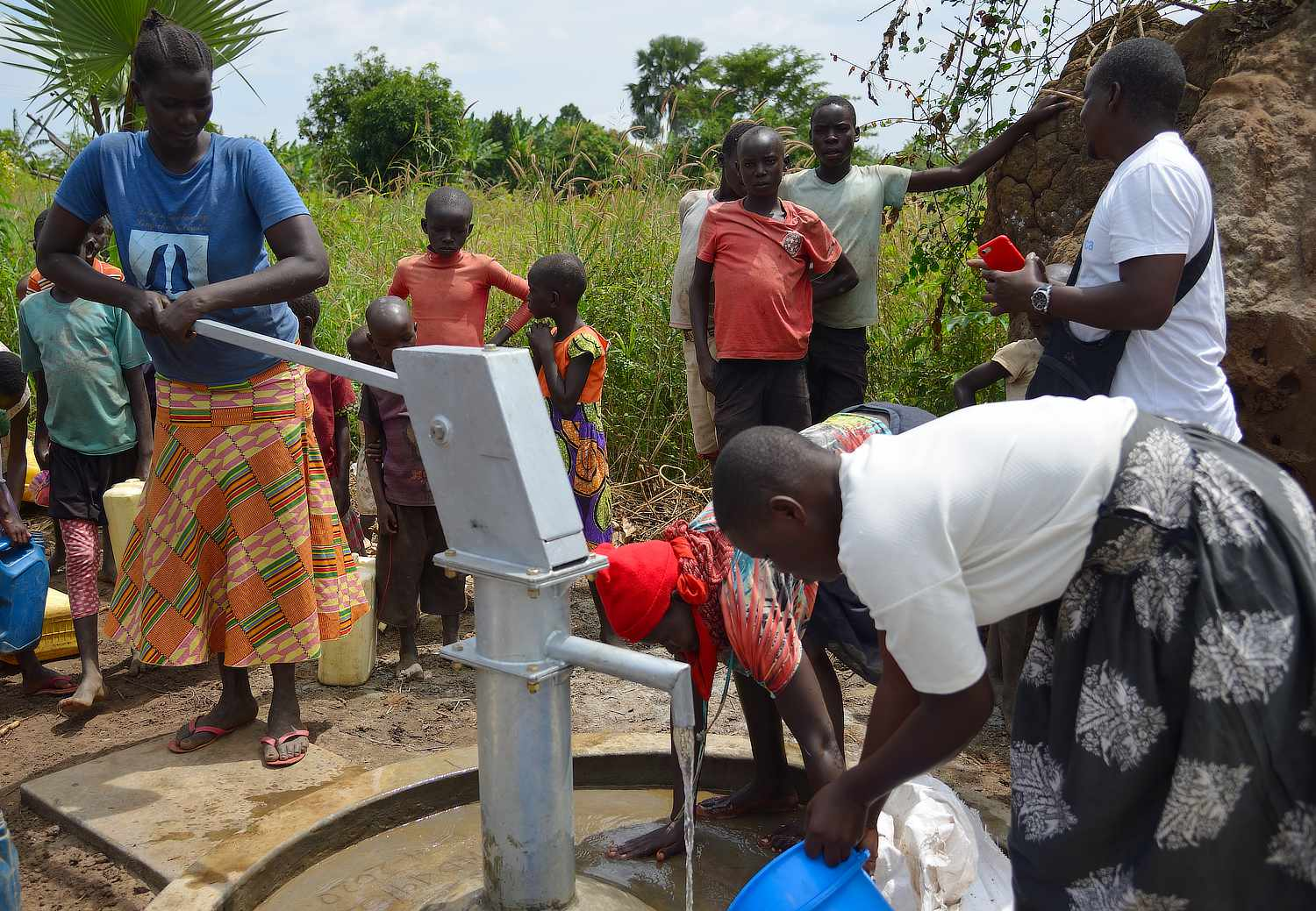 A young lady is pumping the well