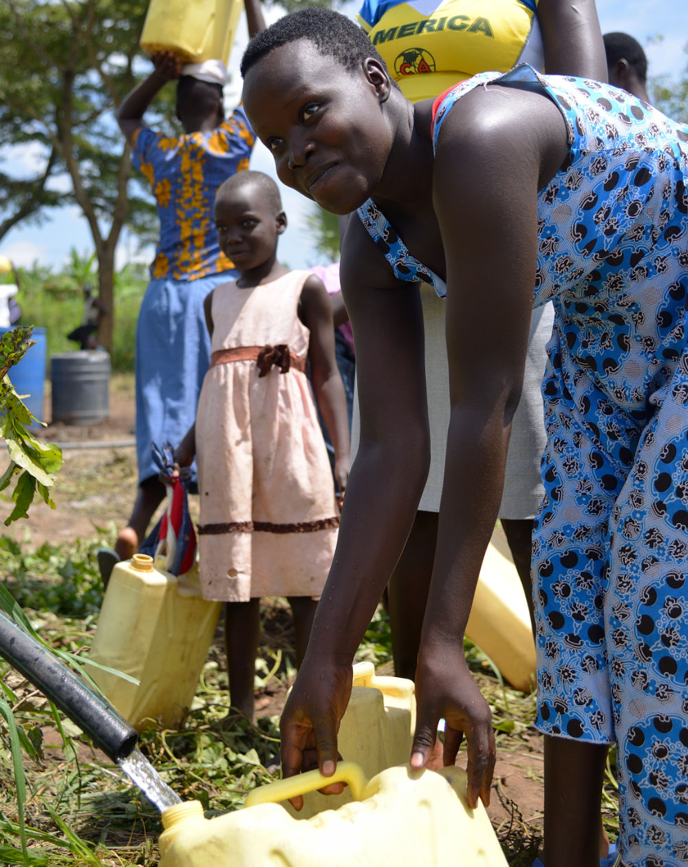 A young lady is fetching water with her cerrycan at hose
