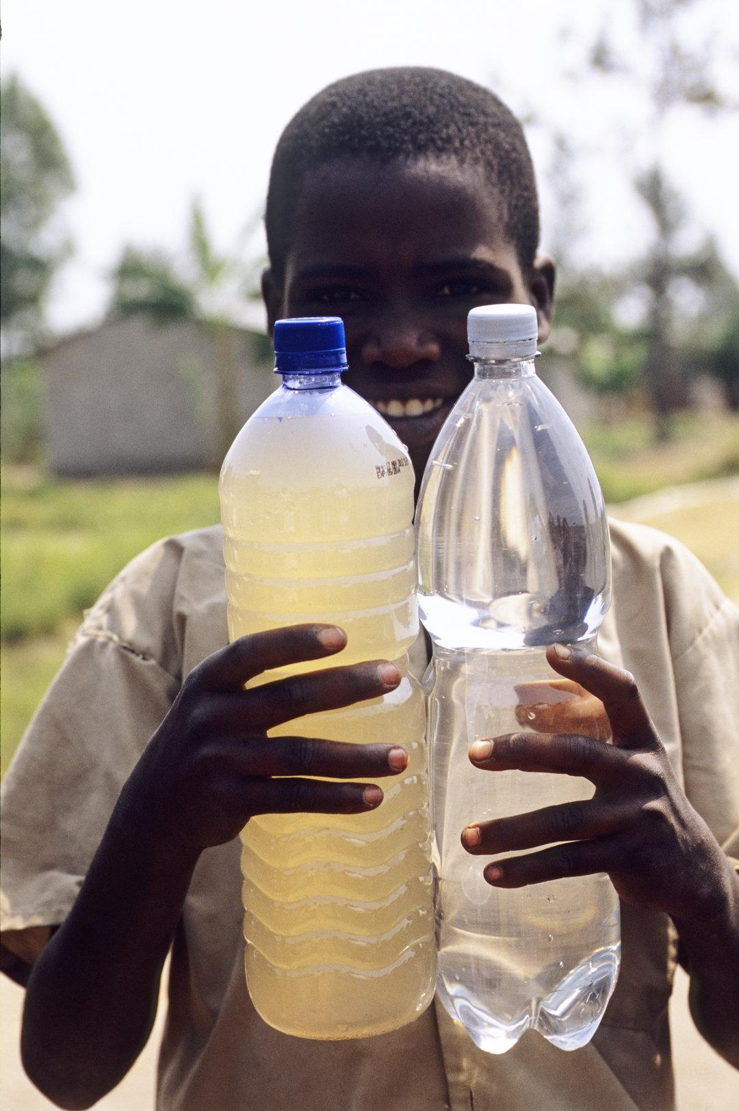 Boy with two bottles in his hands, one with murky water, one with clear water.