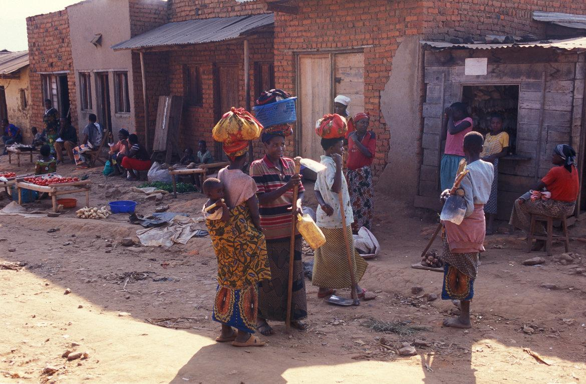 Four women who have been shopping are standing in the village and talking to each other.